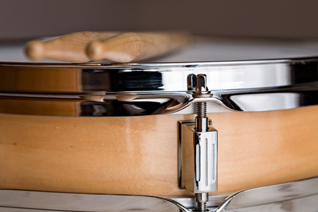snare drum: Close up of a wooden snare drum with drumsticks above