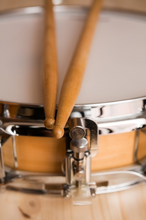 snare drum: Drum sticks over a snare drum with wood background