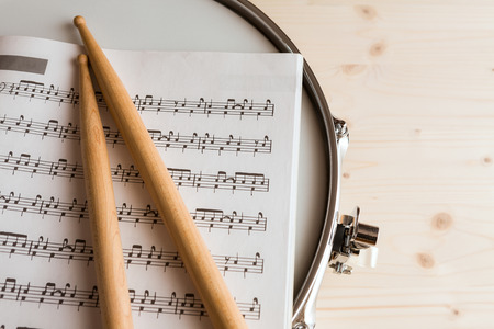 snare drum: Music score and drumsticks over a snare drum with wood background