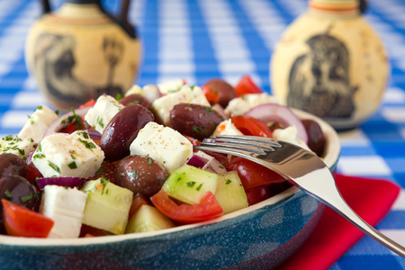 Cerca de ensalada griega con aceitunas queso tomate feta de pepino y cebolla con ánforas griego sobre una servilleta roja