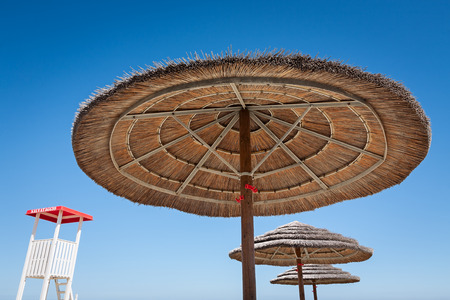 life guard stand: Life guard stand and three beach umbrellas on a blue sky background Stock Photo