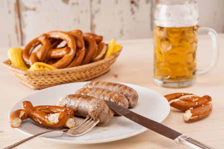 breadbasket: Bavarian cooked sausage and pretzel on a breadbasket and beer on background Stock Photo