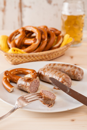 breadbasket: Closeup of bavarian cooked sausage and pretzel on a breadbasket and beer on background Stock Photo