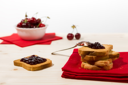 rusk: Rusk with cherry jam and cherry fruit on background