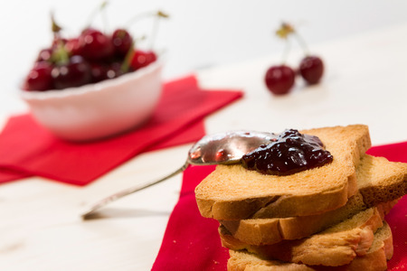 rusk: Closeup of rusk with cherry jam and cherry fruit on background Stock Photo