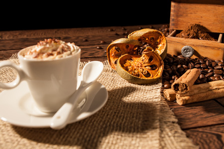 Close-up of coffee cup, dried orange fruit and cinnamon sticks over a wooden background