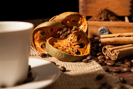 Close-up on dried orange fruit and cinnamon sticks with coffee beans