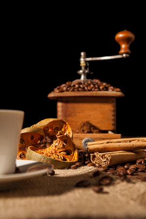 Close-up on dried orange fruit and cinnamon and coffee beans with coffee grinder on background Stock Photo