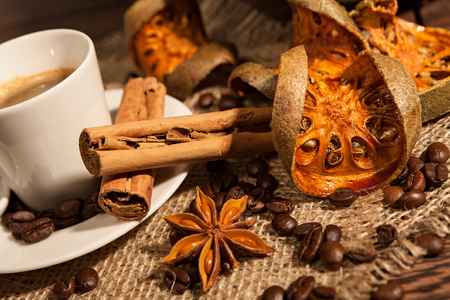 Close-up of cup of coffee with cinnamon, dried orange fruit and star anise