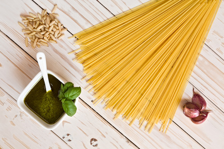Pesto genovese and linguine pasta, pine nuts and garlic on a table seen from above Stock Photo