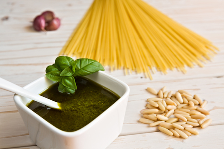 linguine pasta: Closeup of pesto genovese and linguine pasta, pine nuts and garlic on a table