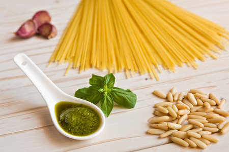 linguine pasta: Closeup of pesto genovese sauce and linguine pasta, pine nuts and garlic on a table