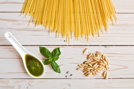 linguine pasta: Pesto genovese sauce and linguine pasta, pine nuts and garlic on a table seen from above