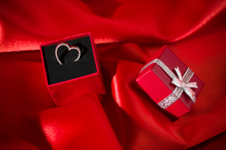 Heart pendant in a red gift box over a red satin background Imagens