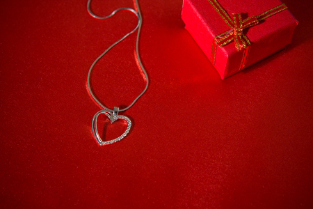 Heart pendant on a red satin background and a gift box Stock Photo