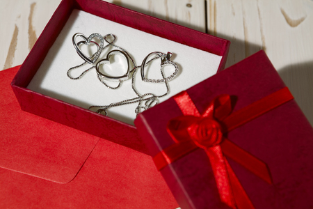 Closeup of silver heart pendants in a red gift box and a red envelope over a wooden background Imagens - 70438805