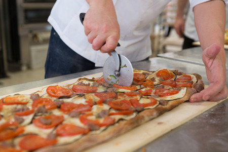 Máquina de cortar pizza focaccia romana con tomate, berenjena y salchicha