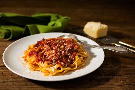 소박한 테이블 위에 bolognese ragu와 Tagliatelle 파스타