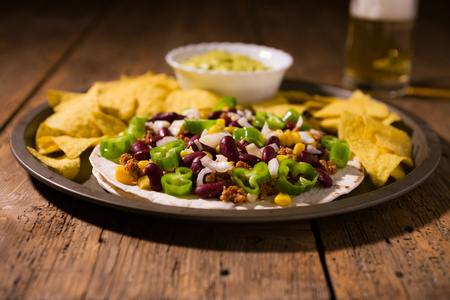 Mexican tortillas with meat, red beans and Jalapeno pepper over an old wooden table