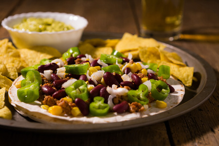 Mexican tortillas with meat, red beans, Jalapeno pepper and nachos chips over an old wooden table