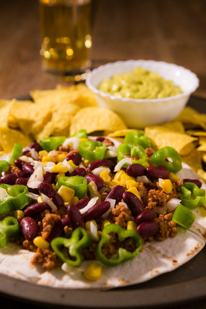 Closeup of Mexican tortillas with meat, red beans, Jalapeno pepper, nachos chips, beer and salsa guacamole over an old wooden table Stock Photo