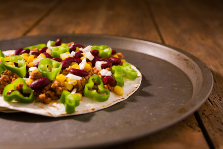 Mexican tortillas with meat, red beans, Jalapeno pepper and onion over a platter