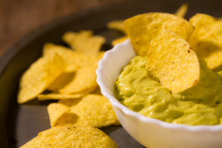 Closeup of salsa guacamole and nachos chips over a platter Stock Photo