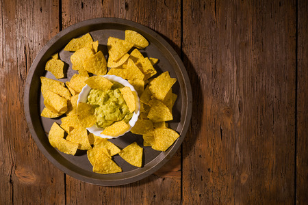 Nachos chips with salsa guacamole on a platter over an old wooden table seen from above