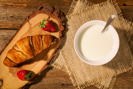 Continental breakfast with croissant, strawberries and a cup of milk seen from above