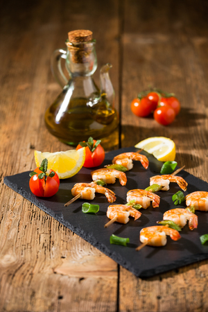 Shrimp skewers with tomatoes, lemon and oil on a stone