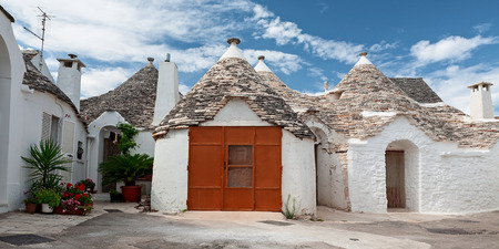 Some Trulli houses in a street of Alberobello in a panoramic view, Puglia, Italy