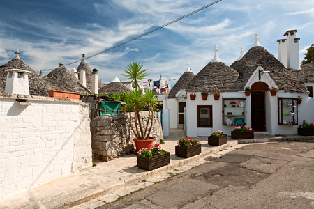 Traditional Trulli houses in Alberobello under a blue sky, Puglia, Italy