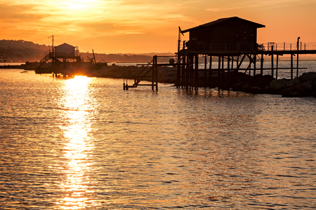 Stilt house over the sea at sunset with the sun reflecting on the water