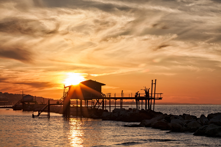 Stilt house over the sea in backlight during a golden sunset Stock Photo