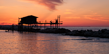 Stilt house over the sea in a beautiful red sunset Stock Photo