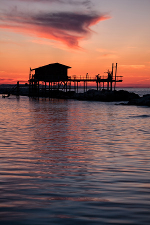 Stilt house in silhouette over the sea in a beautiful red sunset Stock Photo