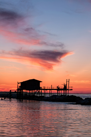 Stilt house in silhouette over the sea during a beautiful red sunset Stock Photo