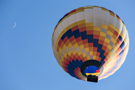 Colorful hot-air balloon in flight and moon seen from below against a blue sky