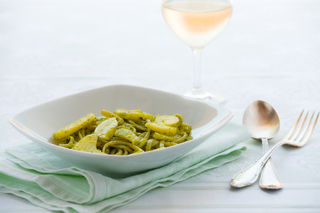 Linguine pasta with pesto genovese and potatoes over a table with cutlery and white wine glass Archivio Fotografico