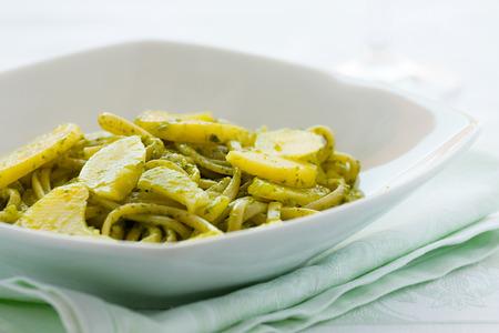 Closeup of linguine pasta with pesto genovese and potatoes over a table Archivio Fotografico