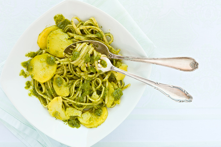 Closeup of linguine pasta with pesto genovese and potatoes over a table with cutlery seen from above