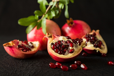 black textured background: Closeup of ripe pomegranate fruits and seeds over a textured black background