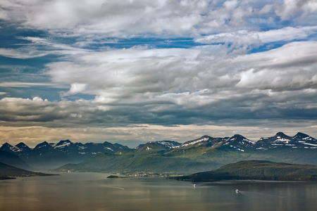 Cloudscape over the mountains in Molde with some boats in the fjord, Norway