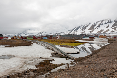 Mountains and wooden houses in a cloudy day in Ny Alesund, Svalbard islands, Norway Stock Photo
