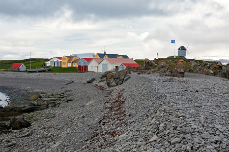 Houses and windmill in Vigur island in a windy day, Iceland