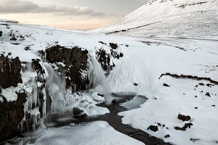 Closeup of waterfall in front of Kirkjufell mountain at sunset in Snaefellsnes peninsula, Iceland