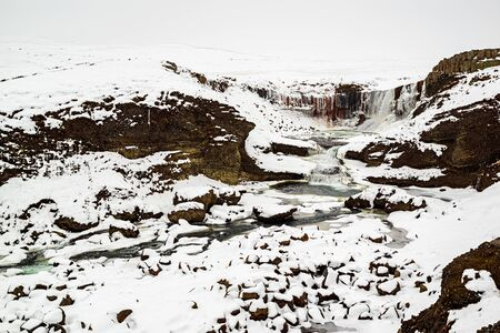 Snaedufoss waterfall during a snowing winter day, Iceland
