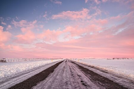 Pink sunset in an iced road in Iceland Stock Photo
