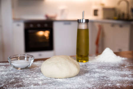 Dough for pizza over a wooden table in a home kitchen