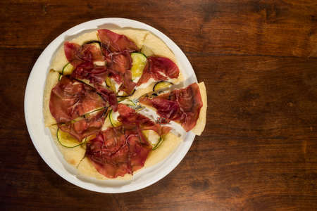Italian pizza with bresaola, zucchini and eggplant seen from above